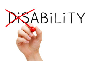 Hand turning the word Disability into Ability with red marker isolated on white.